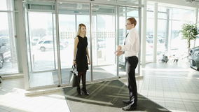 La mujer viene a la sala de exposición donde está en la recepción de la puerta en el distribuidor autorizado metrajes
