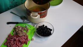 La mujer vierte en las zanahorias ralladas caldo de la carne, pegadas con la salsa de tomate Saltwort de la sopa Los ingredientes almacen de video