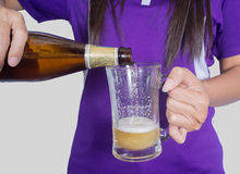 La mujer vierte la cerveza Foto de archivo