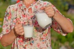 La mujer vierte la leche en vidrio Imagen de archivo
