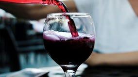 La mujer vierte la limonada de una botella en un restaurante en un vidrio, primer de la soda Cámara lenta almacen de video
