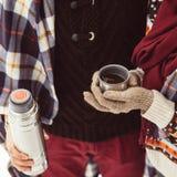 La mujer vierte té de un termo Primer del bosque del invierno Foto de Quadro Abrigo ajustado en mujeres El hombre está vertiendo  Fotos de archivo