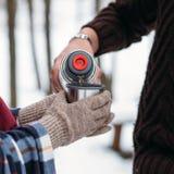 La mujer vierte té de un termo Primer del bosque del invierno Foto de Quadro Abrigo ajustado en mujeres El hombre está vertiendo  Imagen de archivo libre de regalías