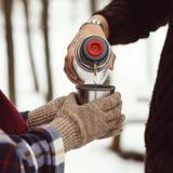 La mujer vierte té de un termo Primer del bosque del invierno Foto de Quadro Abrigo ajustado en mujeres El hombre está vertiendo  Imágenes de archivo libres de regalías