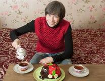 La mujer vierte té en una taza Imagen de archivo