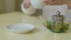 La mujer vierte té verde de la tetera almacen de video
