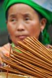 La mujer vietnamita que vende incienso se pega en el mercado de Bac Ha, Vietna Fotografía de archivo libre de regalías