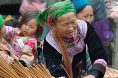 La mujer vietnamita que vende incienso se pega en el mercado de Bac Ha, Vietna Imagen de archivo