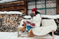 La mujer vistió sentarse caliente fuera de una cabaña en un día de invierno frío Foto de archivo
