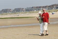 La mujer y el adulto mayores sirven recorrer en la playa Imagen de archivo libre de regalías