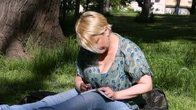 La mujer y el estudiante que se sientan en hierba, toma notas en cuaderno, aprendiendo y escribe pensamientos, escribe el libro metrajes