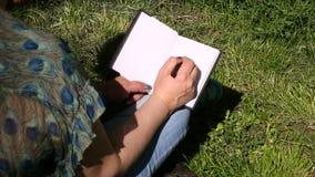 La mujer y el estudiante que se sientan en hierba, toma notas en cuaderno, aprendiendo y escribe pensamientos, escribe el libro almacen de video