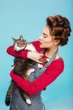 La mujer y el gato presentan para la imagen juntos mientras que limpia Fotos de archivo libres de regalías