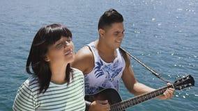 La mujer y el hombre cantan una canción con una guitarra metrajes