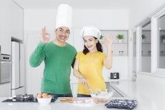 La mujer y el hombre cocinan las galletas con la muestra aceptable Fotos de archivo libres de regalías