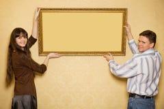 La mujer y el hombre cuelgan para arriba en cuadro de la pared Fotos de archivo libres de regalías