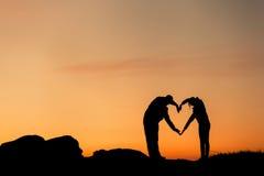 La mujer y el hombre dan la silueta sobre el cielo en el fondo de la puesta del sol Fotos de archivo