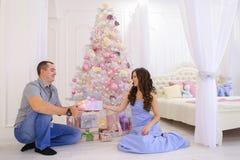 La mujer y el hombre dan a regalos de Navidad su mitad en bedro espacioso Imagenes de archivo