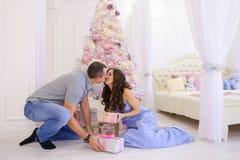 La mujer y el hombre dan a regalos de Navidad su mitad en bedro espacioso Foto de archivo