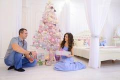 La mujer y el hombre dan a regalos de Navidad su mitad en bedro espacioso Fotografía de archivo