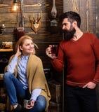 La mujer y el hombre en caras sonrientes disfrutan de la atmósfera acogedora con las bebidas calientes Concepto de la intimidad L fotos de archivo