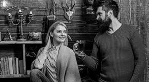 La mujer y el hombre en caras sonrientes disfrutan de la atmósfera acogedora con las bebidas calientes Concepto de la intimidad L imagen de archivo libre de regalías