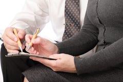 La mujer y el hombre escriben la pluma en el papel aislado Imagen de archivo