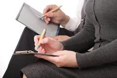 La mujer y el hombre escriben la pluma en el papel aislado Foto de archivo libre de regalías