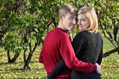 La mujer y el hombre felices abrazan y miran detrás en parque Fotos de archivo