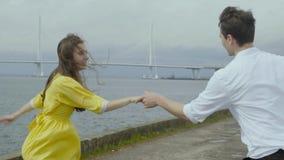La mujer y el hombre felices del yoyng bailan estilo popular en un muelle en un tiempo lluvioso almacen de video