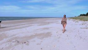 La mujer y el hombre por la playa hacen actividades almacen de video