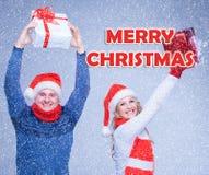 La mujer y el hombre se vistieron en el sombrero de santa que se sostenía con los regalos de una Navidad imagenes de archivo