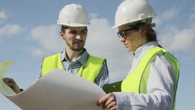 La mujer y el hombre son los ingenieros jefe del proyecto en chalecos verdes almacen de metraje de vídeo
