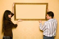La mujer y el hombre sonriente cuelgan para arriba en cuadro de la pared Imagen de archivo libre de regalías