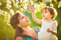 La mujer y el niño felices en la primavera floreciente cultivan un huerto. Kissi del niño Imagen de archivo