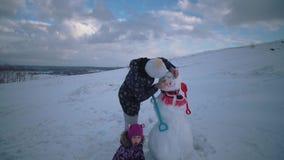 La mujer y el ni?o juntos esculpen un mu?eco de nieve en la colina almacen de metraje de vídeo