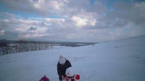 La mujer y el ni?o juntos esculpen un mu?eco de nieve en la colina metrajes
