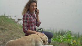 La mujer y el perro bonitos es reclinación al aire libre juntos almacen de metraje de vídeo