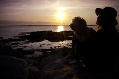 La mujer y el perro disfrutan de puesta del sol de la playa fotografía de archivo libre de regalías