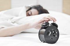 La mujer y el reloj de alarma Fotografía de archivo libre de regalías