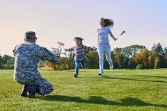 La mujer y la hija están encontrando al soldado en uniforme Fotos de archivo