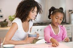 La mujer y la chica joven en cocina con arte proyectan s Foto de archivo