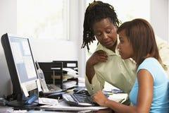 La mujer y la hija utilizan un ordenador Foto de archivo libre de regalías