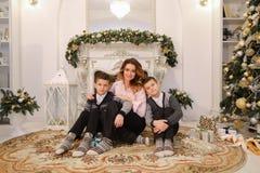 La mujer y la madre y los niños agradables con los muchachos miran y sonríen en c Fotografía de archivo