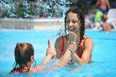 La mujer y la muchacha hermosas sonrientes se baña en piscina Imágenes de archivo libres de regalías