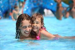 La mujer y la niña sonrientes se baña en piscina Foto de archivo
