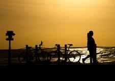 La mujer y las bicis siluetean en la puesta del sol fotografía de archivo libre de regalías