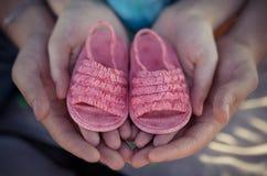 La mujer y las manos jovenes del padre y de la madre del hombre aislaron solamente sostener pocos zapatos de los rosas bebés en a Imágenes de archivo libres de regalías