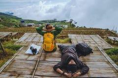 La mujer y los hombres del amante que viajan los asiáticos se relajan en el día de fiesta El mapa de la visión explora las montañ imagenes de archivo