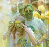 La mujer y los hombres sonrientes cubiertos con color amarillo y verde sacan el polvo de i Fotografía de archivo